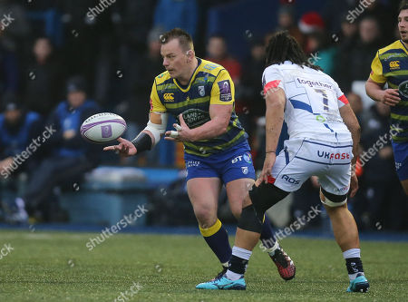 Matthew Rees of Cardiff Blues feeds the ball out as TJ Ioane of Sale Sharks closes in