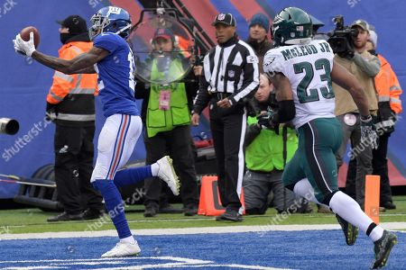 New York Giants wide receiver Tavarres King, left, makes a touchdown catch on pass fro quarterback Eli Manning, not pictured, as Philadelphia Eagles free safety Rodney McLeod (23) looks on during the first half of an NFL football game, in East Rutherford, N.J