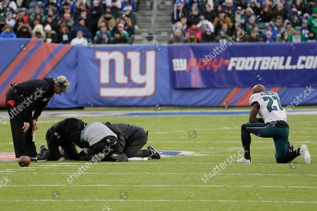 Philadelphia Eagles strong safety Malcolm Jenkins (27) takes a knee as trainers and head coach Doug Pederson, far left, take a look at teammate Patrick Robinson during the second half of an NFL football game against the New York Giants, in East Rutherford, N.J