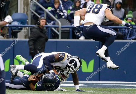 Seattle Seahawks quarterback Russell Wilson (3) is sacked by Los Angeles Rams nose tackle Michael Brockers (90) as Rams' Connor Barwin (98) leaps in the air in the first half of an NFL football game, in Seattle. The Rams won 42-7