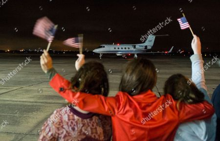 Stock Image of In this photo provided by NASA, astronaut Scott Kelly's girlfriend NASA public affairs representative Amiko Kauderer, center, along with Kelly's daughters Samantha, left and Charlotte, right, wave American flags as the plane carrying Expedition 46 Commander Kelly of NASA taxis upon landing at Ellington Field, in Houston, after his return to Earth. The Soyuz TMA-18M spacecraft landed near the town of Dzhezkazgan, Kazakhstan, on Wednesday with Kelly and Russian cosmonauts Mikhail Kornienko and Sergey Volkov of Roscosmos. Kelly and Kornienko competed an International Space Station record year-long mission to collect valuable data on the effect of long duration weightlessness on the human body that will be used to formulate a human mission to Mars. Volkov is returning after six months on the station