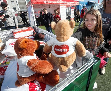Emma Green, 9, picks a bear after participating in a football toss during the Huggies and Help a Mother Out diaper bank diaper drive at Levi's® Stadium on in Santa Clara, Calif. Huggies and the San Francisco 49ers teamed up for the second year to combat diaper need with #HuddleUpWithHuggies for San Francisco's Biggest Diaper Drive event to help Bay Area families in need
