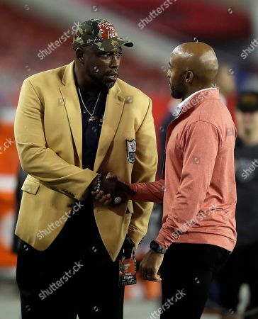 Former Tampa Bay Buccaneers' Warren Sapp, let, and Ronde Barber, shake hands before an NFL football game against the Atlanta Falcons, in Tampa, Fla