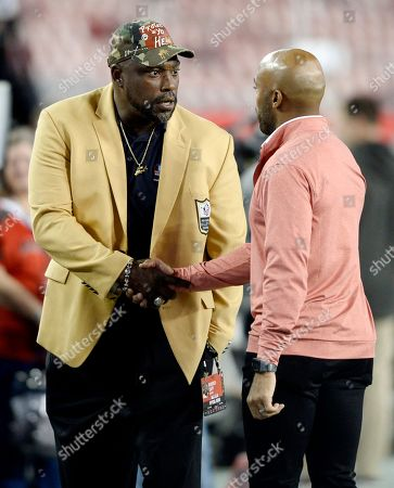 Former Tampa Bay Buccaneers Warren Sapp and Rhonde Barber talk prior to an NFL football game, in Tampa, Fla