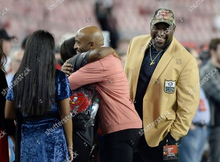 Former Tampa Bay Buccaneers Rhonde Barber and Warren Sapp prior to an NFL football game, in Tampa, Fla