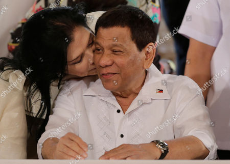 """Philippine President Rodrigo Duterte is kissed by congresswoman Rose Marie """"Baby"""" Arenas during the ceremonial signing of 2018 General Appropriations Act and Tax Reform for Acceleration and Inclusion Bill at the Malacanang Presidential Palace in Manila, Philippines on"""