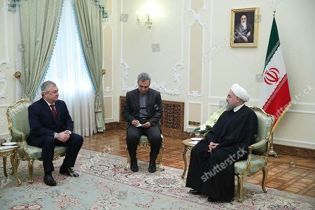 In this photo released by an official website of the office of the Iranian Presidency, Iran's President Hassan Rouhani, right, meets with Russian Deputy Foreign Minister and Russia's special envoy on Syria Alexander Lavrentiev, left, at his office, in Tehran, Iran, . An unidentified interpreter sits at center