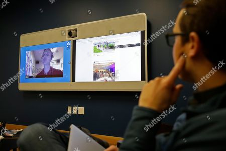 Stock Image of Jeff Wieland, right, Facebook director of accessibility, watches as engineer Matt King, who is blind, demonstrates facial recognition technology via a teleconference at Facebook headquarters in Menlo Park, Calif. Facebook is unveiling a new AI-powered feature just in time for alcohol-filled holiday parties: you can now see untagged pictures of your face on your friend's news feeds and ask the poster to remove them