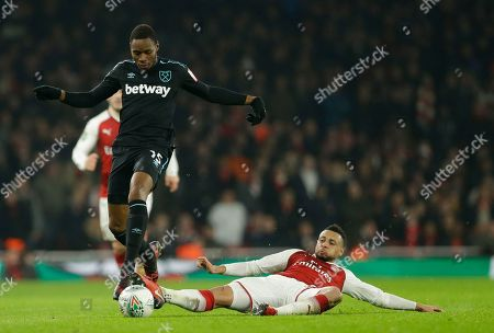 West Ham United's Diafra Sakho, left avoids the sliding tackle of Arsenal's Francis Coquelin during the English League Cup quarterfinal soccer match between Arsenal and West Ham United at the Emirates stadium in London