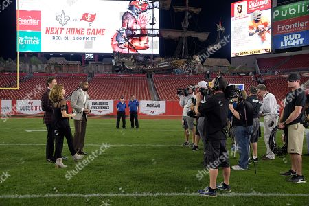 Suzy Kolber, Steve Young, Charles Woodson. ESPN's Monday Night Football crew of Steve Young, left, Suzy Kolber, second from left, and Charles Woodson broadcast from the field after an NFL football game between the Tampa Bay Buccaneers and the Atlanta Falcons, in Tampa, Fla. The Falcons won 24-21