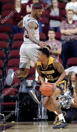 Stock Photo of Duane Wilson, Lavone Holland II. Texas A&M guard Duane Wilson (13) goes up as Northern Kentucky guard Lavone Holland II (30) looks to pass under during the first half of an NCAA college basketball game, in College Station, Texas