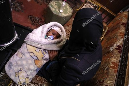 Stock Image of Karim's aunt, an infant who was injured twice from bombings on Eastern al-Ghouta, holds him, rebel-held Douma, Syria, 20 December 2017. On 29 October 2017 Fadya, a Syrian woman who was displaced from al-Qisa, took her three-months old child Karim Abdul Rahman from Beit Sawa (a small area with no markets in eastern al-Ghouta) to Hamoria in order to buy home supplies, during her shopping the market with bombed by forces allegedly loyal to the Syrian regime, which led to her death and her son Karim, lost his eye. After spending 10 days at a hospital he was discharged to his house, in which another bombing led to a shrapnel to injure his skull. Activists worldwide launched a campaign in solidarity with Karim as a symbol for the besiegement of Eastern al-Ghouta, hundreds joined the campaign globally on social media on #SolidarityWithKarim, including the British ambassador to the UN Matthew Rycroft.