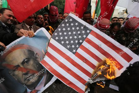 Palestinian supporters of the Popular Front for the Liberation of Palestine (PFLP) burn posters depicting Israeli President Benyamin Netanyahu, an Israeli flag and a U.S. flag during a protest against U.S. President Donald Trump's decision to recognise Jerusalem as the capital of Israel, in Gaza City