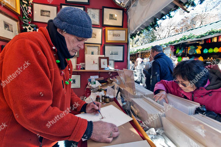 Stephen Francis Duffy, a painter and printmaker from Hobart, N.Y., prepares to gild one of his etchings, as a customer searches his art in his booth at the Union Square Holiday Market, in New York. At the holiday markets that pop up annually, many of the booths are staffed by artisans hoping to make a significant portion of their revenue or to get visibility that will translate into sales other times of the year