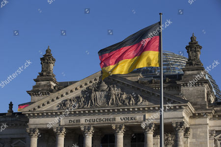 "Reichstag - a German flag flutters in front of the Reichstag, with a detail of the inscription ""Dem Deutschen Volke"", ""[To] the German people"", and the Norman Foster designed glass dome."