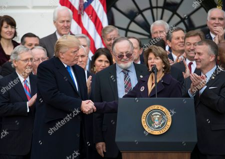 Stock Photo of Donald Trump, Daniel Sullivan, Lisa Murkowski, Mitch McConnell, Don Young. President Donald Trump shakes hands with Sen. Lisa Murkowski, R-Alaska, as she speaks during an event on the South Lawn of the White House in Washington, to acknowledge the final passage of tax overhaul legislation by congress. Also on stage are Senate Majority Leader Mitch McConnell of Ky., Rep. Don Young, R-Alaska, and Sen. Dan Sullivan, R-Alaska, right