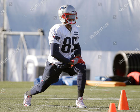 Stock Image of New England Patriots wide receiver Kenny Britt stretches while warming up during an NFL football practice, in Foxborough, Mass