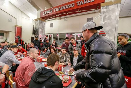 A magician performs card tricks at the Lewis Training Table facility at the University of Nebraska in Lincoln, Neb., where athletes can dine on specially made entrees such as mahi mahi steaks, bison meatloaf or chicken marsala. The hundreds of millions of dollars that have poured into the Power Five conferences, much of it from television rights fees, have enriched dozens of schools and allowed them to give their athletes the best of everything, right down to what they eat every day