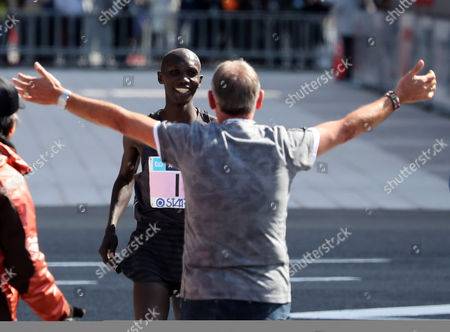 Wilson Kipsang of Kenya (L) is greeted by his coach as he crossed the finish line