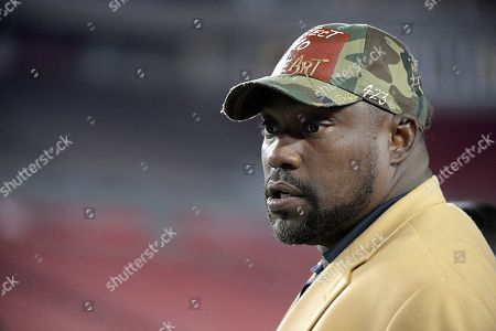 Former Tampa Bay Buccaneers defensive lineman Warren Sapp watches players warm up on the field before an NFL football game against the Atlanta Falcons, in Tampa, Fla