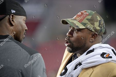 Warren Sapp, Bryant Young. Former Tampa Bay Buccaneers defensive lineman Warren Sapp, right, talks with Atlanta Falcons defensive line coach Bryant Young on the field before an NFL football game between the two teams, in Tampa, Fla