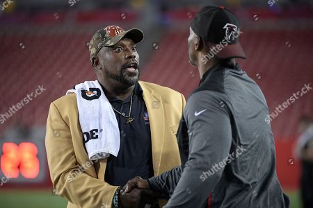Warren Sapp, Bryant Young. Former Tampa Bay Buccaneers defensive lineman Warren Sapp, left, talks with Atlanta Falcons defensive line coach Bryant Young on the field before an NFL football game between the two teams, in Tampa, Fla