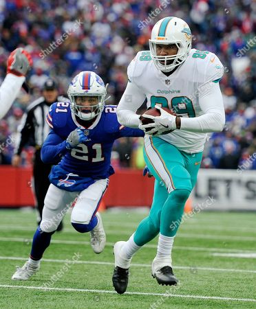 Miami Dolphins tight end Julius Thomas (89) is pursued by Buffalo Bills safety Jordan Poyer (21) during the second half of an NFL football game, in Orchard Park, N.Y. Buffalo beat Miami 24-16