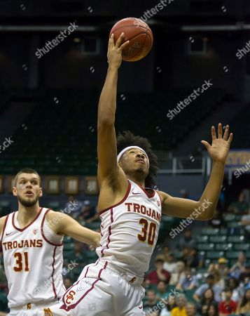 Elijah Stewart, Nick Rakocevic. Southern California guard Elijah Stewart (30) controls a rebound while teammate forward Nick Rakocevic (31) looks on during the first half of an NCAA college basketball game against Akron at the Diamond Head Classic tournament, in Honolulu