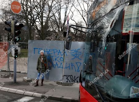 """A woman stands by a graffiti that reads """"General Ratko Mladic"""" and a cross with four Cyrillic letters for """"S"""" which means: """"Only Unity saves the Serb"""", in Belgrade, Serbia, . A U.N. court has convicted former Bosnian Serb military chief Gen. Ratko Mladic of genocide and crimes against humanity and sentenced him to life in prison for atrocities perpetrated during Bosnia's 1992-1995 war"""