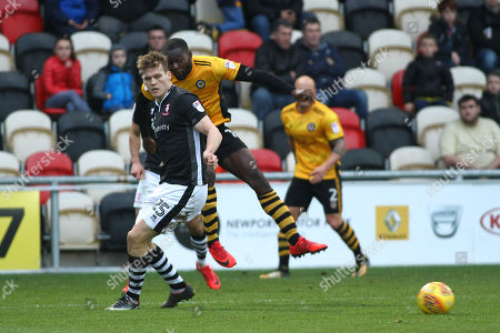 Frank Nouble of Newport County has a shot blocked by Sean Raggett of Lincoln City