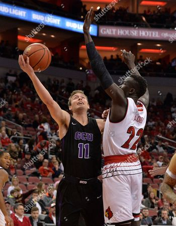 Stock Picture of Casey Benson, Deng Adel. Grand Canyon guard Casey Benson (11) attempts a shot over the defense of Louisville forward Deng Adel (22) during the first half of an NCAA college basketball game, in Louisville, Ky