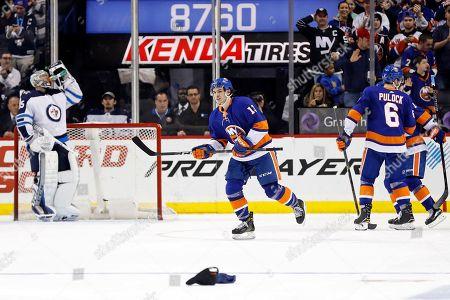 New York Islanders' Mathew Barzal skates past Winnipeg Jets goalie Steve Mason after scoring his third goal of the game in the third period of an NHL hockey game, in New York. The Islanders won 5-2