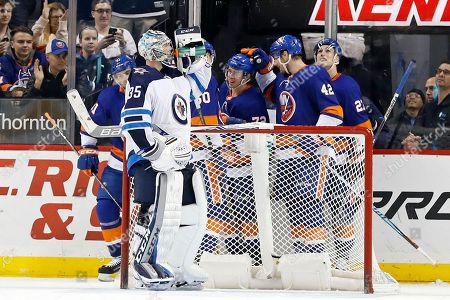 Steve Mason, Anthony Beauvillier. Winnipeg Jets goalie Steve Mason takes a drink of water as New York Islanders' Anthony Beauvillier, center, celebrates scoring a goal with teammates in the third period of an NHL hockey game, in New York. The Islanders won 5-2