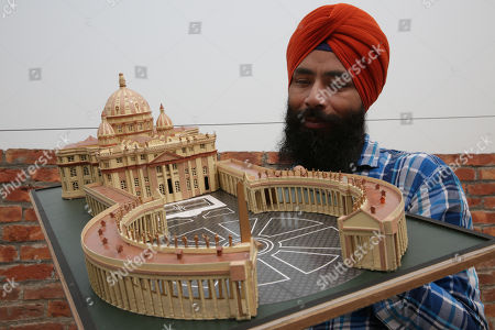 Indian paper artist Gurpreet Singh displays his creation, a miniature paper replica of the Vatican Basilica of St. Peter, made for the occasion of Christmas, in Amritsar, India, 24 December 2017. According to Singh, it took him two and a half months to make the paper model. The model is 13 inches wide, nine inches in height and 31 inches in length.