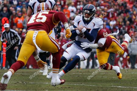 Brock Osweiler, Junior Galette. Denver Broncos quarterback Brock Osweiler (17) is tackled by Washington Redskins linebacker Junior Galette (58) as linebacker Pete Robertson (45) close in during the first half an NFL football game in Landover, Md