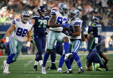 Stock Photo of Tyrone Crawford, Benson Mayowa, Anthony Hitchens, Russell Wilson. Dallas Cowboys defensive end Tyrone Crawford (98), Benson Mayowa (93) and Anthony Hitchens (59) celebrates Mayowa's sack of Seattle Seahawks' Russell Wilson, right rear bottom in the first half of an NFL football game, in Arlington, Texas