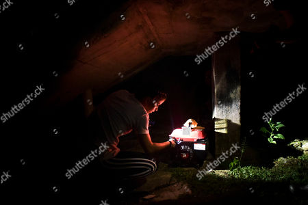 Barrio Patron resident Karina Santiago Gonzalez works on a small power plant in Morovis, Puerto Rico. More than three months have passed since Hurricane Maria. Neighbors start blowing out candles and turning off generators as they go to bed around 9 p.m., having nothing else to do in the dark except sleep