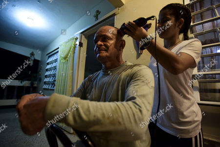 56 year old Jose Luis Gonzalez gets a haircut on his balcony by Karina Santiago Gonzalez in Barrio Patron, Morovis, Puerto Rico. Lights are twinkling across more neighborhoods in the U.S. territory, but uncertainty, depression and anger is growing among the 30,000 people in the small mountain town of Morovis nestled in the center of the island that remains in the dark