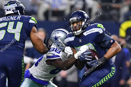 Seattle Seahawks linebacker K.J. Wright (50) tries to get away from Dallas Cowboys wide receiver Dez Bryant (88) after making an interception during an NFL football game between the Seattle Seahawks and the Dallas Cowboys at AT&T Stadium in Arlington, Texas