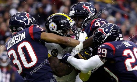 Andre Hal, Joel Heath, Kevin Johnson, Le'Veon Bell. Pittsburgh Steelers running back Le'Veon Bell, center, is wrapped up by Houston Texans' Kevin Johnson (30), Joel Heath (93) and Andre Hal (29) during the first half of an NFL football game, in Houston