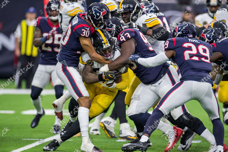 Houston Texans cornerback Kevin Johnson (30) and Houston Texans defensive end Joel Heath (93) tackle Pittsburgh Steelers running back Le'Veon Bell (26) during the 1st quarter of an NFL football game between the Houston Texans and the Pittsburgh Steelers at NRG Stadium in Houston, TX. The Steelers won the game 34 to 6
