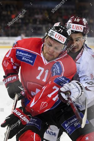 Team Suisse player Richard Tanner, left, fights for the puck with Riga's Mikelis Redlihs, during the game between Team Suisse and Dinamo Riga at the 91th Spengler Cup ice hockey tournament in Davos, Switzerland, Tuesday, December 26, 2017.