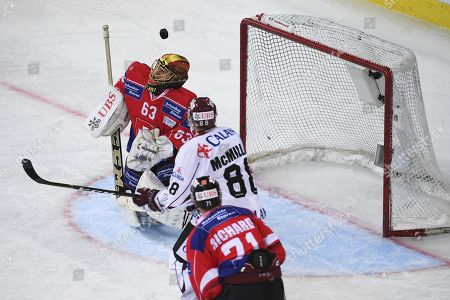 Team Suisse goalkeeper Leonardo Genoni, left, and Riga's Brandon McMillan fight for the puck, during the game between Team Suisse and Dinamo Riga at the 91th Spengler Cup ice hockey tournament in Davos, Switzerland, Tuesday, December 26, 2017.