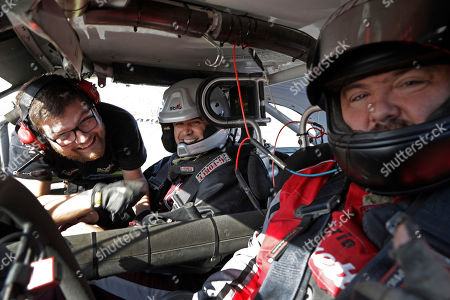 Texas A&M's interim head coach Jeff Banks, center, smiles as he is strapped into a NASCAR race car before taking laps during an event at Charlotte Motor Speedway before the Belk Bowl NCAA college football game in Concord, N.C., . Wake Forest faces Texas A&M in the Belk Bowl on Friday, Dec. 29, 2017