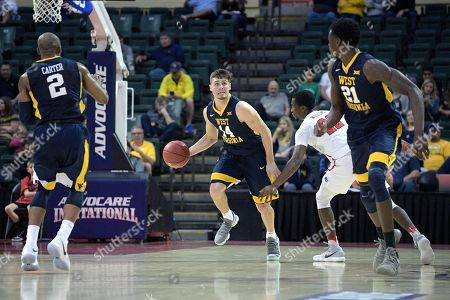 Chase Harler, Austin Williams. West Virginia guard Chase Harler (14) pushes the ball up the court in front of Marist guard Austin Williams (22) during the first half of an NCAA college basketball game at the AdvoCare Invitational tournament, in Lake Buena Vista, Fla