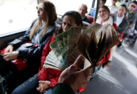 In this Dec. 12, 2017 photo, Venezuelan national Jorge Gutierrez holds a wad of worthless Venezuelan currency as he rides a public bus in Bogota, Colombia, . Gutierrez wants to exchange his bolivars for Colombian pesos. An estimated 550,000 Venezuelans have migrated to Colombia. Of those, some 200,000 have crossed over just in the last six months, threatening to overwhelm Colombia's limited resources