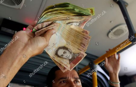 In this Dec. 12, 2017 photo, Venezuelan national Jorge Gutierrez holds a wad of worthless Venezuelan currency that he wants to exchange for some Colombian money, as he rides a bus in Bogota, Colombia, . Eager to find work abroad, Gutierrez arrived in October with his wife, baby daughter, and a backpack crammed full with 2 million bolivars that he saved up. The stash of bills, however, amounted to just $20, so he kept it