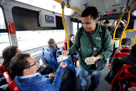 Stock Picture of Venezuelan national Jorge Gutierrez hands a 100 bolivar Venezuelan bill to a passenger, as he attempts to sell his Venezuelan currency in exchange for a few Colombian pesos on a bus in Bogota, Colombia. Gutierrez holds up the the nearly worthless currency of his crisis-riddled home country and asks for a small donation in exchange for each 100 note