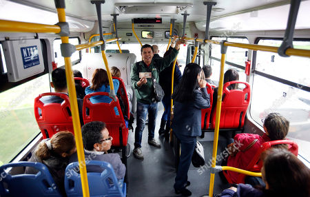 Venezuelan national Jorge Gutierrez holds a bill of Venezuelan currency as he rides a bus in Bogota, Colombia. Giving away a few bolivars as a novelty can earn him roughly $20 in a day, equivalent to the same amount of cash he brought when he migrated to Colombia