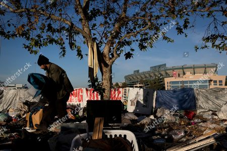"""Homeless Junior Sanchez, 29, carries a tarp he found in a pile of trash in a homeless encampment on the Santa Ana River trail near Angel Stadium, in Anaheim, Calif. """"Toughest part being homeless is getting a plate of food and a shower,"""" said Sanchez who said he became homeless after losing his job as cook"""